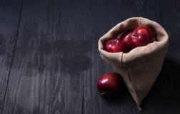 Manzanas rojas puestas en la tabla de madera negra fotografía de archivo libre de regalías