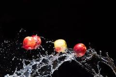Manzanas rojas, volando en espacio con el agua Fotos de archivo libres de regalías