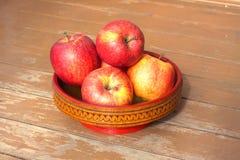 Manzanas rojas y amarillas maduras en primer de madera del cuenco Foto de archivo libre de regalías