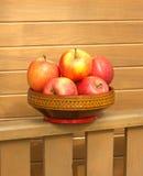 Manzanas rojas y amarillas maduras en primer de madera del cuenco Imagen de archivo libre de regalías