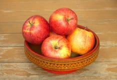 Manzanas rojas y amarillas maduras en primer de madera del cuenco Fotos de archivo