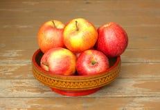Manzanas rojas y amarillas maduras en primer de madera del cuenco Fotos de archivo libres de regalías