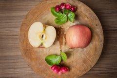 Manzanas rojas y carunda rojo en tabla de cortar de madera Foto de archivo libre de regalías