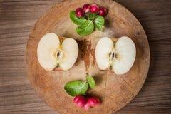 Manzanas rojas y carunda rojo en tabla de cortar de madera Imagenes de archivo