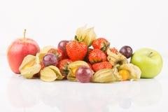 Manzanas rojas y verdes con el physalis anaranjado, las uvas púrpuras y las fresas rojas Imágenes de archivo libres de regalías
