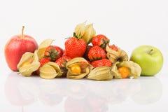 Manzanas rojas y verdes con el physalis anaranjado y las fresas rojas Fotos de archivo libres de regalías