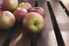 Manzanas rojas y verdes en la tabla de madera rústica Imágenes de archivo libres de regalías