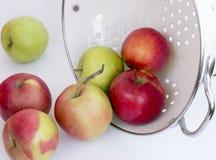 Manzanas rojas y verdes en un collander/un cuenco Imagen de archivo