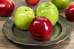 Manzanas rojas y verdes en una placa de metal Foto de archivo libre de regalías