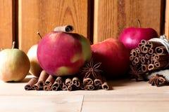 Manzanas rojas y verdes frescas, palillos de canela en fondo de madera Imagen de archivo libre de regalías