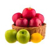 Manzanas rojas y verdes, y limón en una cesta de madera Imágenes de archivo libres de regalías