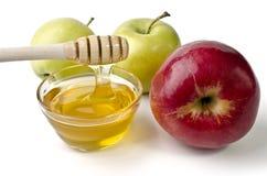 Manzanas rojas y verdes y un cuenco de miel Foto de archivo libre de regalías