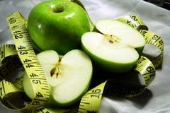 Manzanas verdes con el golpecito de medición Imágenes de archivo libres de regalías