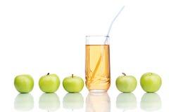 Manzanas verdes con el jugo aislado en blanco Imágenes de archivo libres de regalías