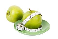 Manzanas verdes con la cinta de medición en la placa verde Foto de archivo
