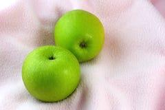 Manzanas verdes en el paño rosado Foto de archivo libre de regalías
