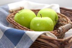 Manzanas verdes en la cesta de mimbre marrón Imagen de archivo