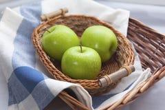 Manzanas verdes en la cesta de mimbre marrón Imágenes de archivo libres de regalías