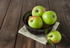 Manzanas verdes en un cuenco en un fondo de madera Imagen de archivo