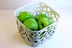 Manzanas verdes en una cesta blanca Imagenes de archivo