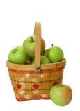 Manzanas verdes en una cesta sobre blanco Imágenes de archivo libres de regalías