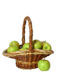 Manzanas verdes en una cesta sobre blanco Fotos de archivo