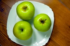 Manzanas verdes en una placa fotos de archivo