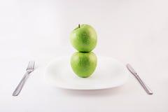 Manzanas verdes en una placa Imagenes de archivo