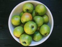 manzanas verdes en una placa blanca en un fondo negro Fotos de archivo libres de regalías
