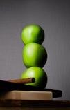 Manzanas verdes en una tabla verticalmente en un tablero de madera Fotografía de archivo