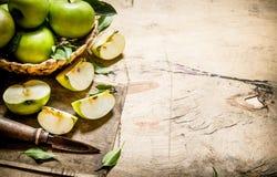 Manzanas verdes frescas en la cesta con el cuchillo Foto de archivo