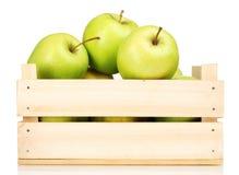 Manzanas verdes jugosas en un embalaje de madera Fotos de archivo