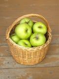Manzanas verdes maduras en primer de la cesta de mimbre Fotos de archivo libres de regalías