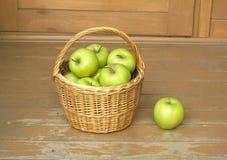Manzanas verdes maduras en primer de la cesta de mimbre Imagen de archivo libre de regalías