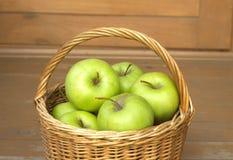 Manzanas verdes maduras en primer de la cesta de mimbre Imagen de archivo