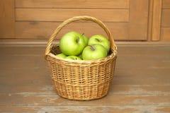 Manzanas verdes maduras en primer de la cesta de mimbre Imagenes de archivo