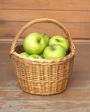 Manzanas verdes maduras en primer de la cesta de mimbre Fotos de archivo