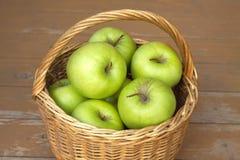 Manzanas verdes maduras en primer de la cesta de mimbre Fotografía de archivo