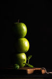 Manzanas verdes que hacen la pila o la torre con la rama de la menta fresca en fondo negro Imágenes de archivo libres de regalías