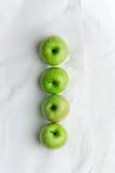 Manzanas verdes sobre el paño blanco Fotos de archivo libres de regalías