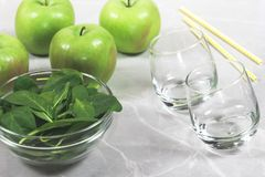 Manzanas verdes, un cuenco de hojas frescas de la espinaca, dos vidrios vacíos y paja imagen de archivo libre de regalías