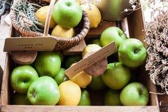 Manzanas verdes y limones amarillos en una caja de madera Foto de archivo libre de regalías