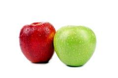 Manzanas verdes y rojas con descensos del agua. Imagen de archivo