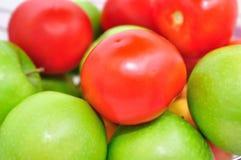 Manzanas verdes y tomates rojos. Foto de archivo