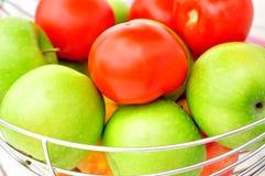 Manzanas verdes y tomates rojos. Imagenes de archivo