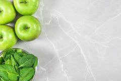 Manzanas verdes y un cuenco de hojas frescas de la espinaca con el espacio de la copia imagenes de archivo
