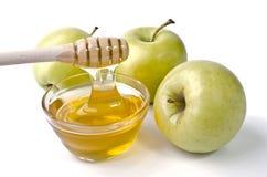 Manzanas verdes y un cuenco de miel Foto de archivo libre de regalías