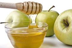 Manzanas verdes y un cuenco de miel Imágenes de archivo libres de regalías