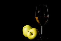 Manzanas y copa de vino verdes con el jugo en negro Imagenes de archivo