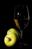 Manzanas y copa de vino verdes con el jugo en negro Fotos de archivo libres de regalías